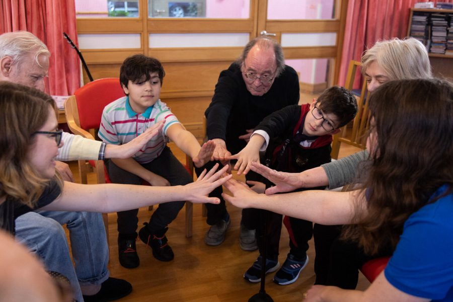Children and elderly people touching hands in BitterSuite's The Many